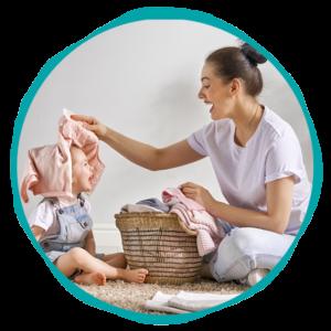Empleada del Hogar jugando con un niño mientras recoge la ropa - Empleada en casa